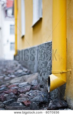 yellow downtake tube in street of old town in Tallinn Estonia (extremely shallow depth of field focus on front tube) poster