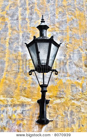 old lantern on yellow wall in street of Tallin old town Estonia poster