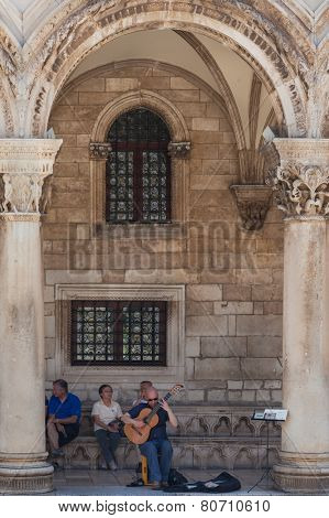 DUBROVNIK, CROATIA - MAY 28, 2014: Man plays guitar in front of Rector's palace. Palace used to serve as seat of the Rector of the Republic of Ragusa and today is the museum.