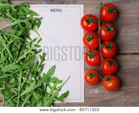 Menu sheet of paper with cherry tomatoes and arugula on rustic wooden surface background
