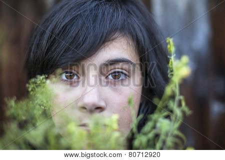 Closeup of black-haired teen girl with expressive eyes, hidden in the greenery of the garden. Emo.