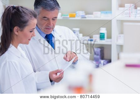 Pharmacist explaining a prescription to his trainee in the pharmacy