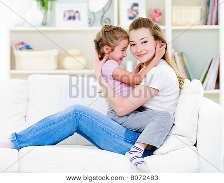Mother With Daughter Sitting On The Sofa