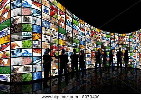 People Looking At Wall Of Screens