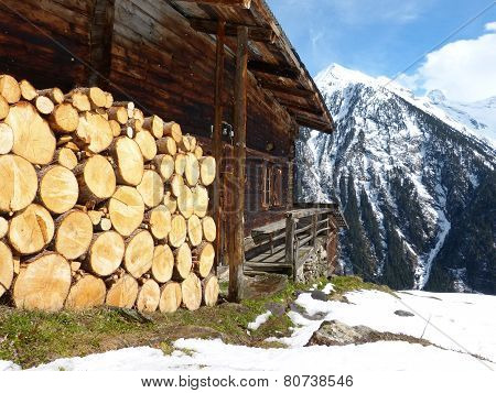 Firewood at the ski hut in alpine winter landscape