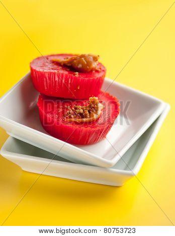 Kutsinta - a Filipino sweet rice cakes in white plates on bright yellow background.