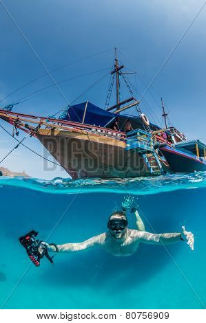 Snorkeller underneath a boat in tropical waters