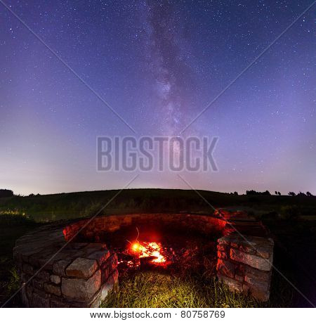 Firepit in the countryside with starry skies in the background