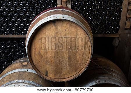 Oak Barrels With Wine Bottles