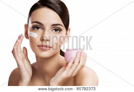 Beautiful young woman applying moisturizing creme, skin care concept