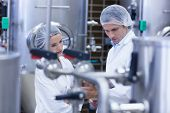 Biologist team talking and wearing hairnet in the factory poster