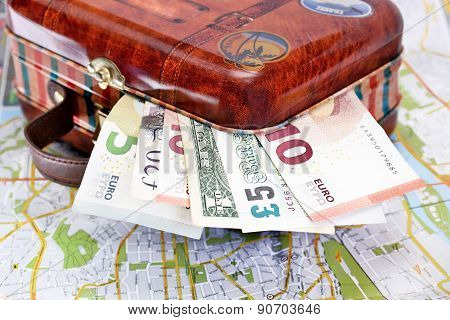 Suitcase with various money Euro Dollar Pound on a map. Travel Tourism concept