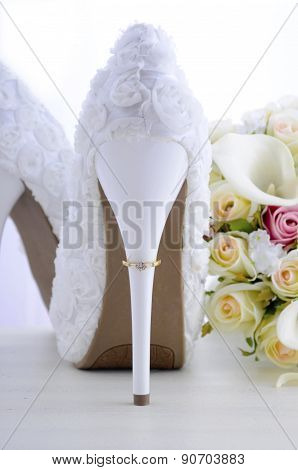 Wedding Day concept with rings on heel of beautiful white floral bridal stiletto shoes with bouquet on white shabby chic wood table. poster