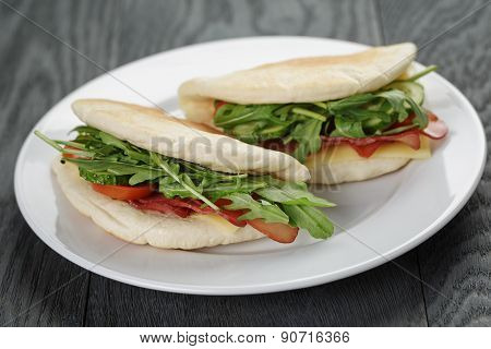 two sandwiches with ham arugula and tomatoes in pita bread on plate, on wood table