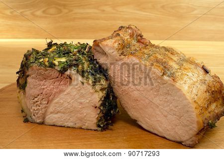 Two Various Pieces Of Baked Meat On A Round Board.
