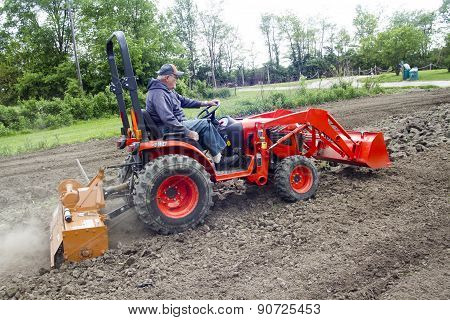 Older Farmer Tilling His Garden