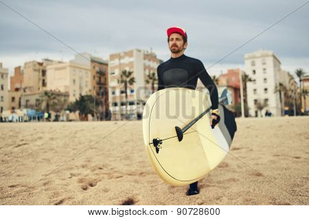 Young Surfer Sports Man Wearing Surfing Neoprene Waterproof Suits And Carrying His Surfing Board