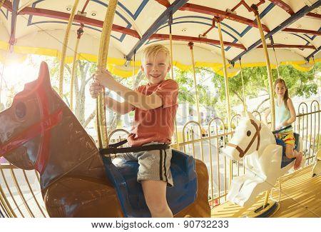 Two cute kids having fun while riding a carousel at an amusement park or carnival