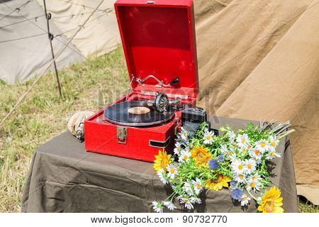 gramophone with a plate camera and flowers on the table