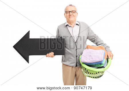 Senor gentleman holding a laundry basket full of clean clothes and a big black arrow pointing left isolated on white background