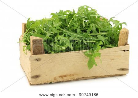 fresh rucola leaves (Eruca sativa) in a wooden box on a white background