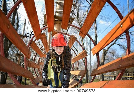 Teen Girl Crawling In A Round Wooden Maze In The Park In The Spring