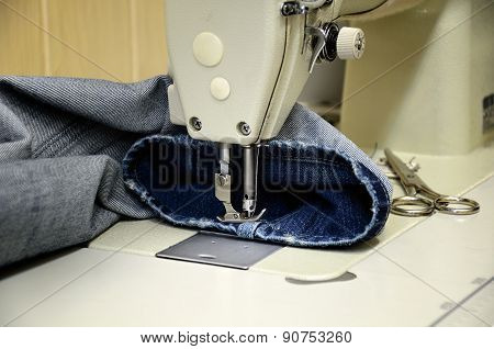 sewing machine and jeans in sewing workshop. horizontal poster