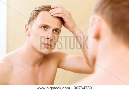 Topless man fixing hair in front of mirror