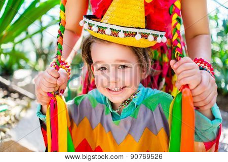 smiling little boy holding his mother braids