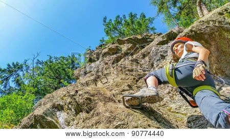 Young woman climber on via ferrata in Alps