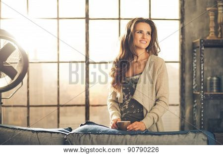 Casual Brunette With Coffee Smiling In Loft Apartment