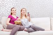 Movie night. Two young beautiful girls sitting on a white couch watching a movie while holding remote control and eating popcorn at pajama party full length poster