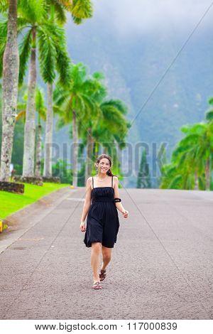 Beautiful Biracial Teen Girl Walking Along Palm Tree Lined Road
