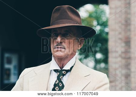 Close-up Of Senior Dandy With Hat And Suit In Front Of Gate.