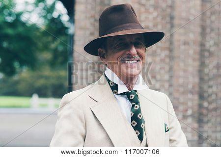 Smiling Senior Dandy In Front Of Gate.