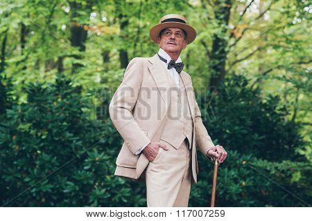 Wealthy Senior Man In Suit Standing With Cane In Garden.