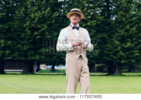 Senior Dandy Taking Cigarette Out Of Silver Container In Garden.