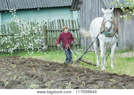 Young farmer tilling soil with traditional single-sided ploughing