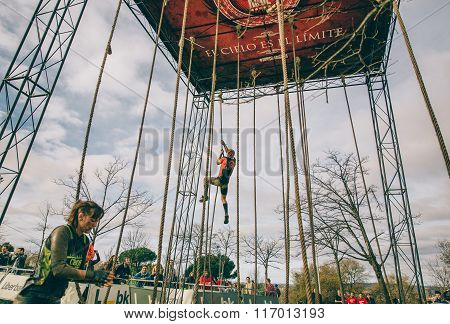 Runner climbing rope in a test of obstacle race