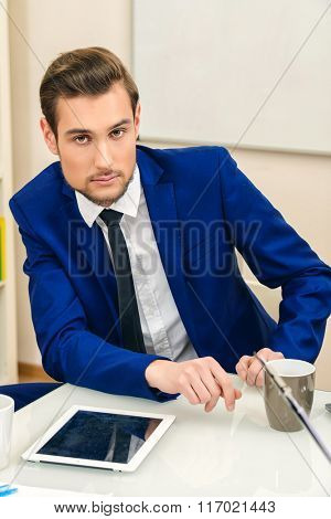 Handsome businessman sitting at his workplace at the modern office.