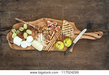 Wine appetizers set: cheese selection, honey, grapes, almonds, walnuts, bread sticks, figs on olive
