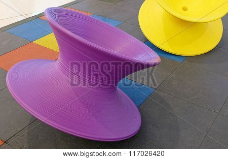 Purple And Yellow Spinning Tops In Kid Playground