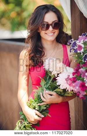 Beautiful brunette with a bouquet of pink flowers