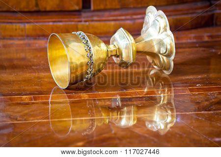 Golden Grail Turned On Wooden Background