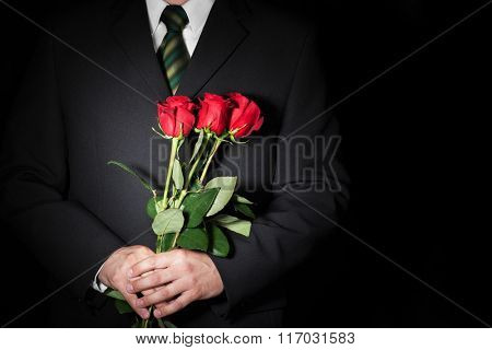 Man holding red roses. Valentine's day concept. Space for text.