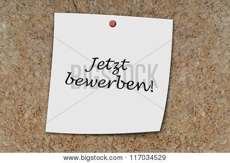 Jetzt bewerben (german apply now) written on a memo pinned on a cork board poster