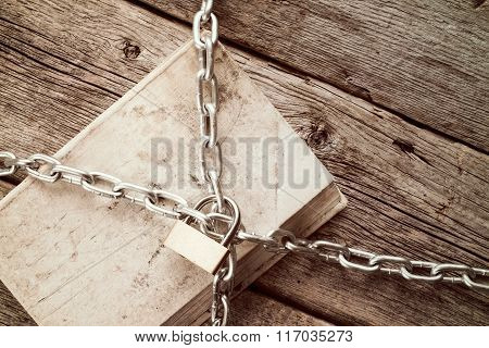 Chained Book On Wooden Background
