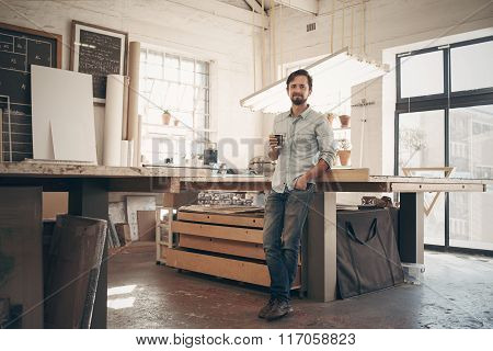 Young designer in his workshop with a cup of coffee