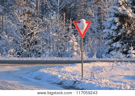 Snowcovered Give Way Warning Sign On A Highway Crossing