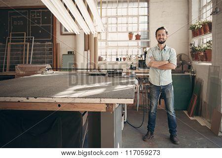 Confident designer standing in his workshop studio